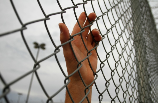 An inmate serving a jail sentence rests his hand on a fence at Maricopa County's Tent City jail in Phoenix